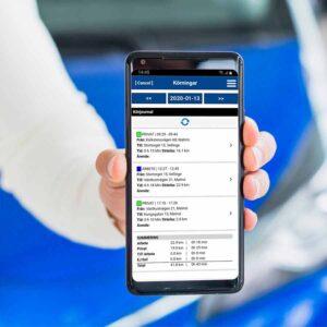 Hand som håller en mobil med körjournalsinformation på skärmen