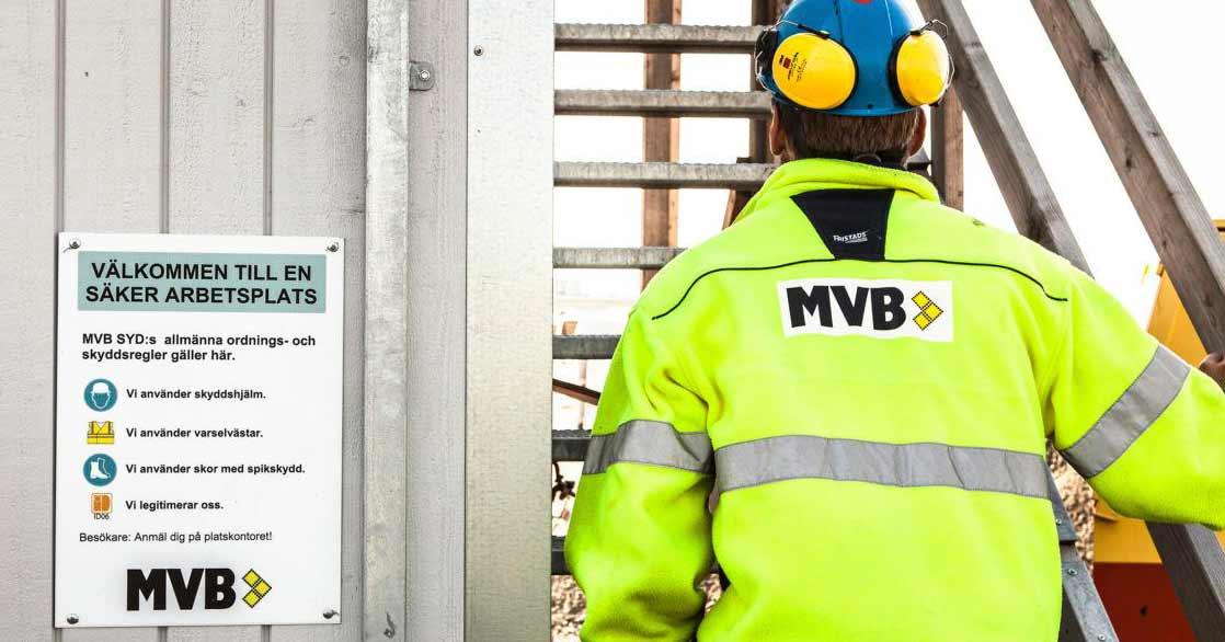 Grå byggbod med metalltrappa. Manlig byggarbetare iklädd gul arbetsjacka, blå hjälm och gula hörselskydd som syns bakifrån gå upp för trappan.