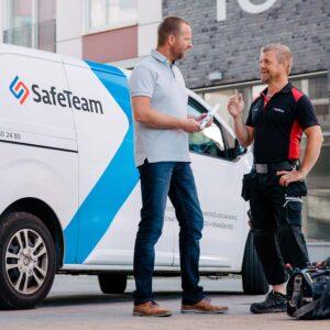 Manlig hantverkare i svarta arbetskläder och en man i grå piké T-shirt och blåjeans samtalar framför en vit servicebil och en grå tegelhusbyggnad.