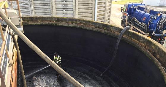 Man i svarta och gula arbetskläder står i en stor cement cistern och spolar rent med en vattenslang.