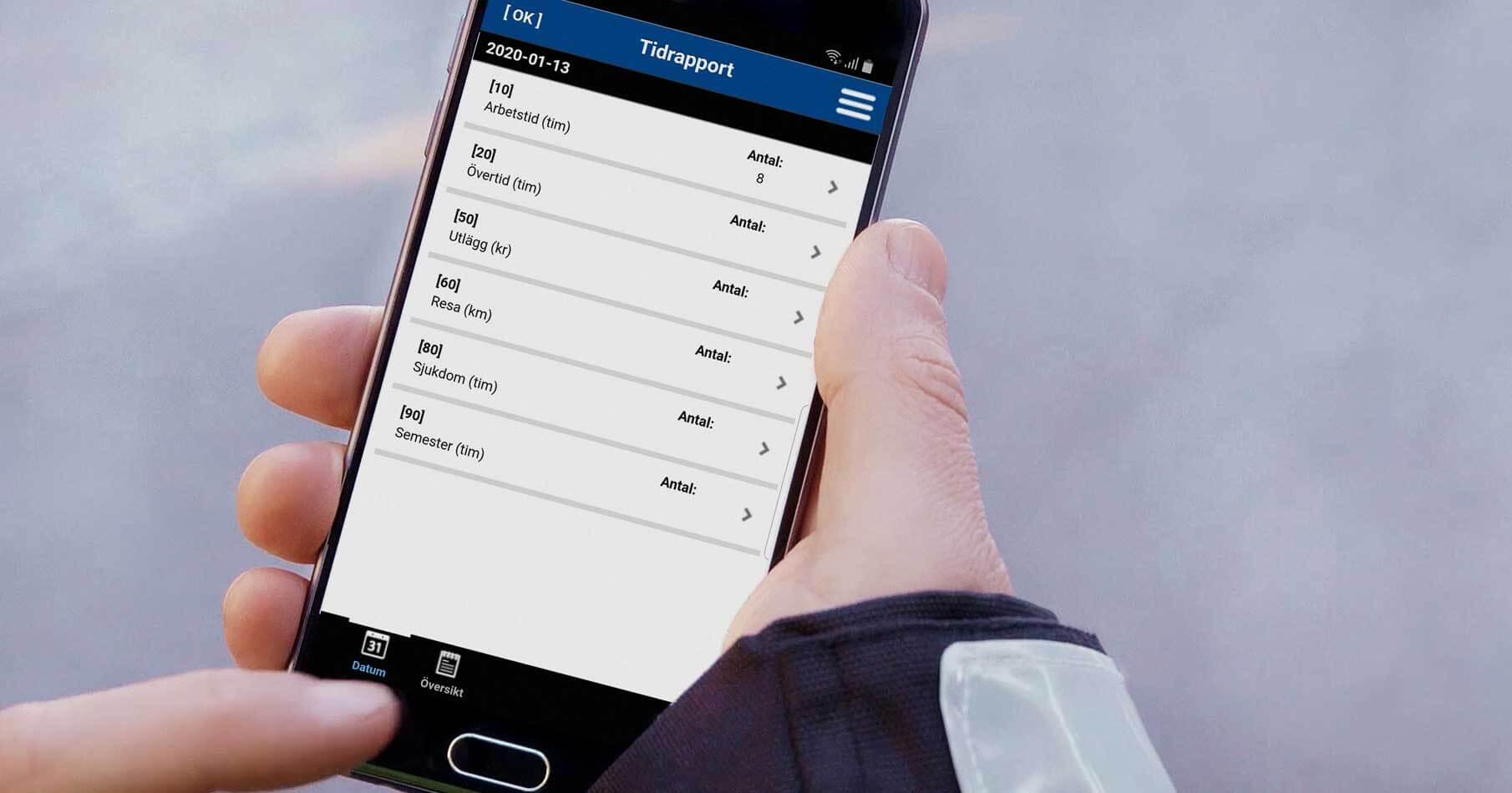 Närbild på fältarbetares händer som tidrapporterar i AddMobiles app för tidrapportering.