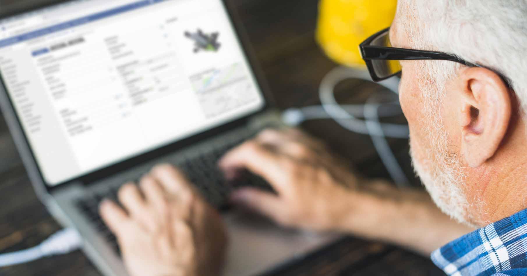 Äldre man med grått hår, skägg samt glasögon sittandes vid ett skrivbort och tittar på verktygsinventering i sin laptop.