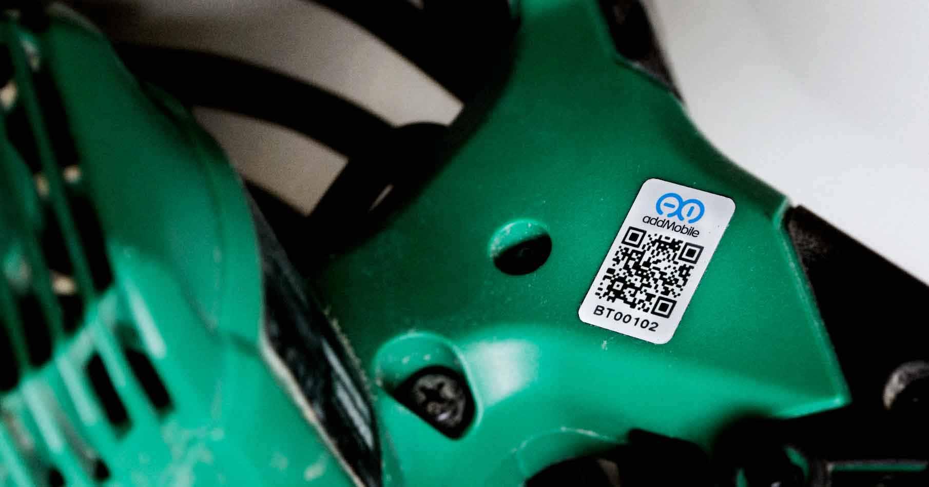 Närbild på en grön handmaskin med en påklistrad QR-kod i vitt.