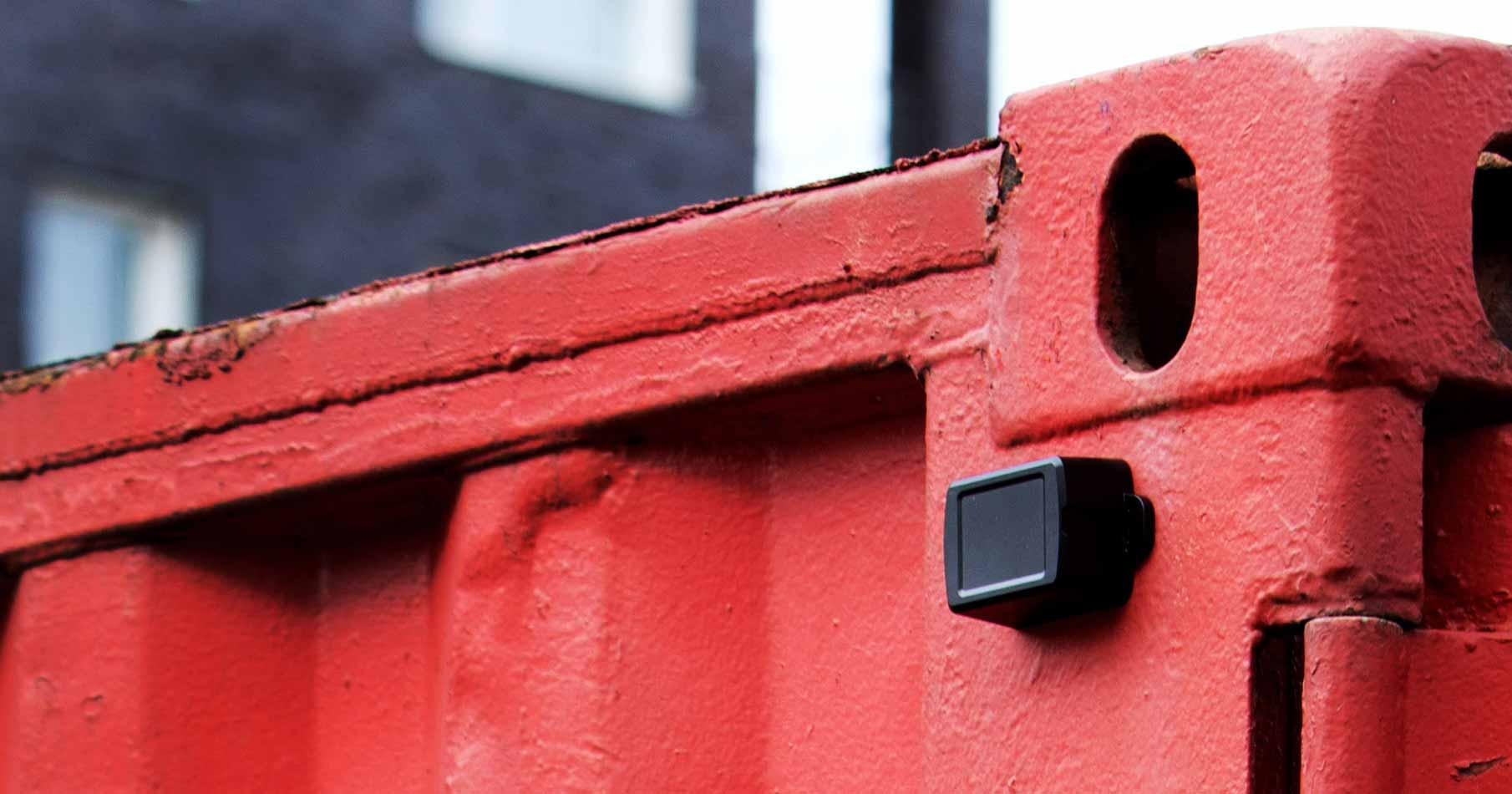Närbild på toppen av en röd container med en monterad svart GPS.