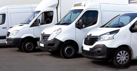 Närbild på fyra vita stora skåpbilar uppradade på en parkeringsplats.