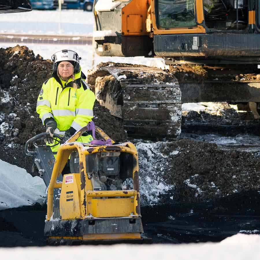 Kvinnlig byggarbetare i gul jacka ute på snötäckt byggarbetsplats med en grävskopa i bakgrunden.