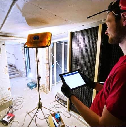 Manlig elektriker som tittar på en digital arbetsordern i sin surfplatta. Han står i en källare som byggs om.