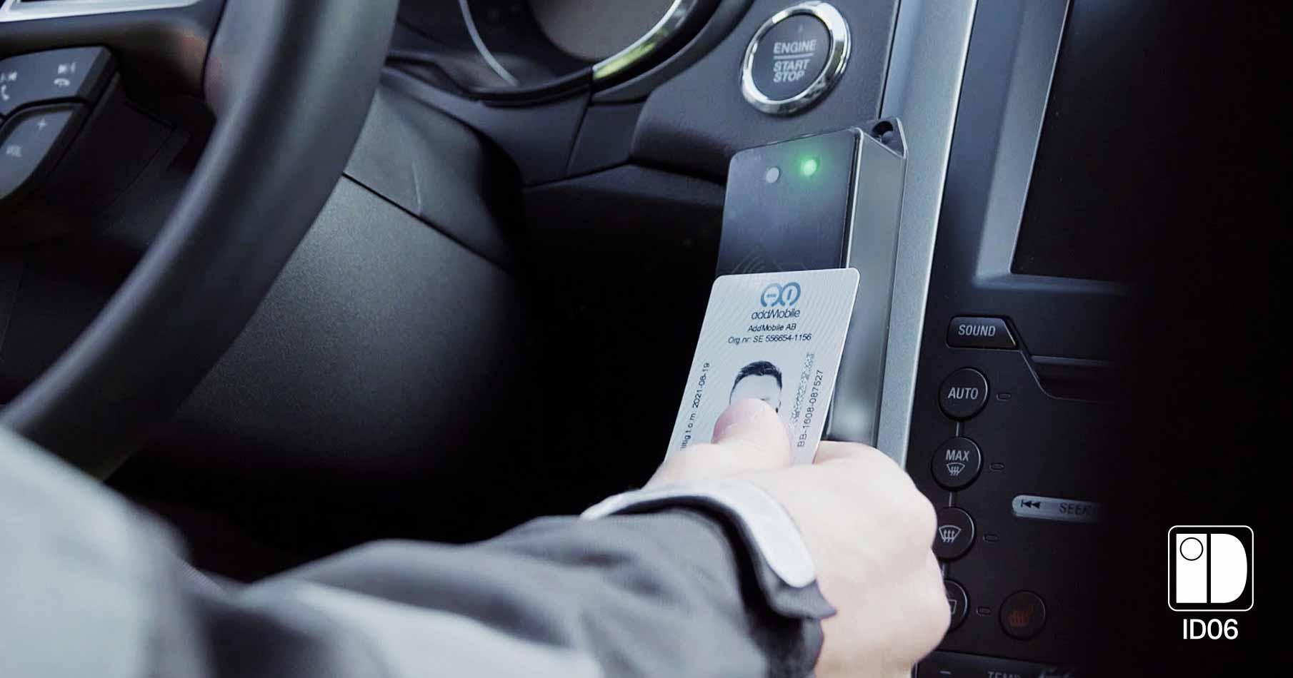 Närbild på en svart kortläsare i personbild och en förare som lagt sitt ID06-kort på kortläsaren