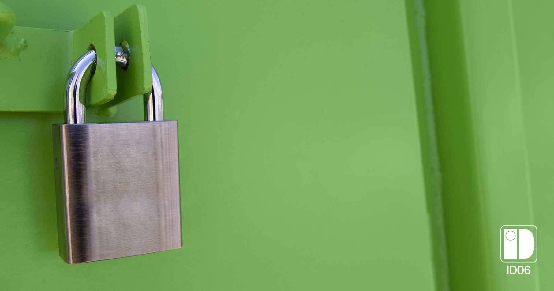 Metallfärgat hänglås i närbild på en grön container