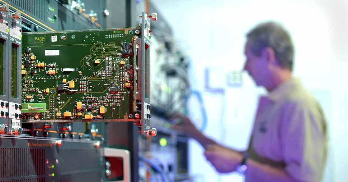 Serverskåp med synligt kretskort i förgrunden och en man i beige T-shirt som servar serverskåpet i bakgrunden.