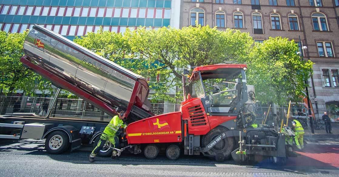 Byggarbetare i gula arbetskläder som asfalterar på en stadsväg med en röd asfaltsmaskin.