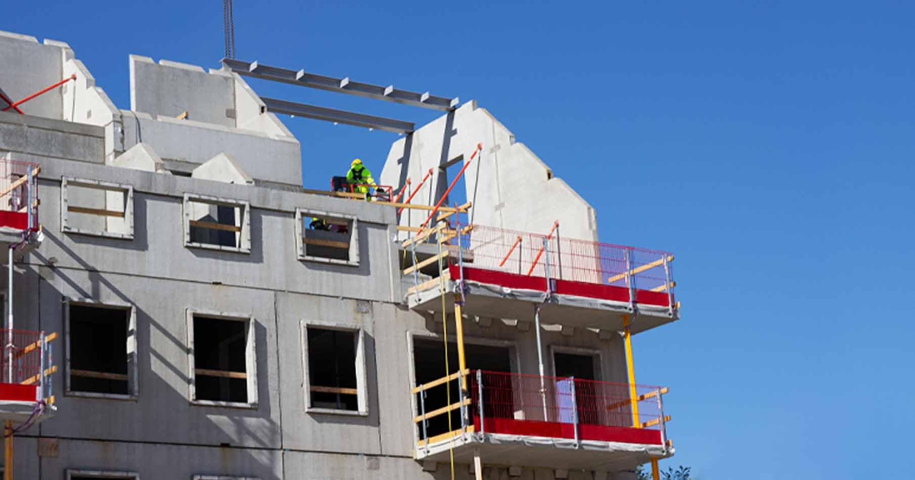 Översta delen av ett lägenhetshus som byggs mot blå himmel. Byggarbetare med gula arbetskläder på taket.
