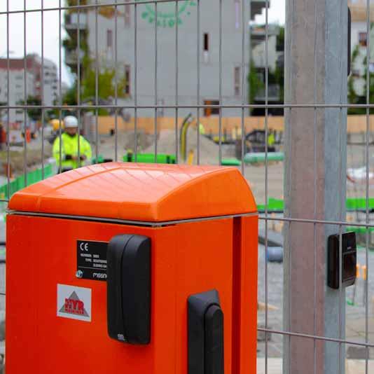 Orange styrbox på ett staket till en byggarbetsplats med en manlig byggarbetare med gula arbetskläder och vit hjälm i bakgrunden.