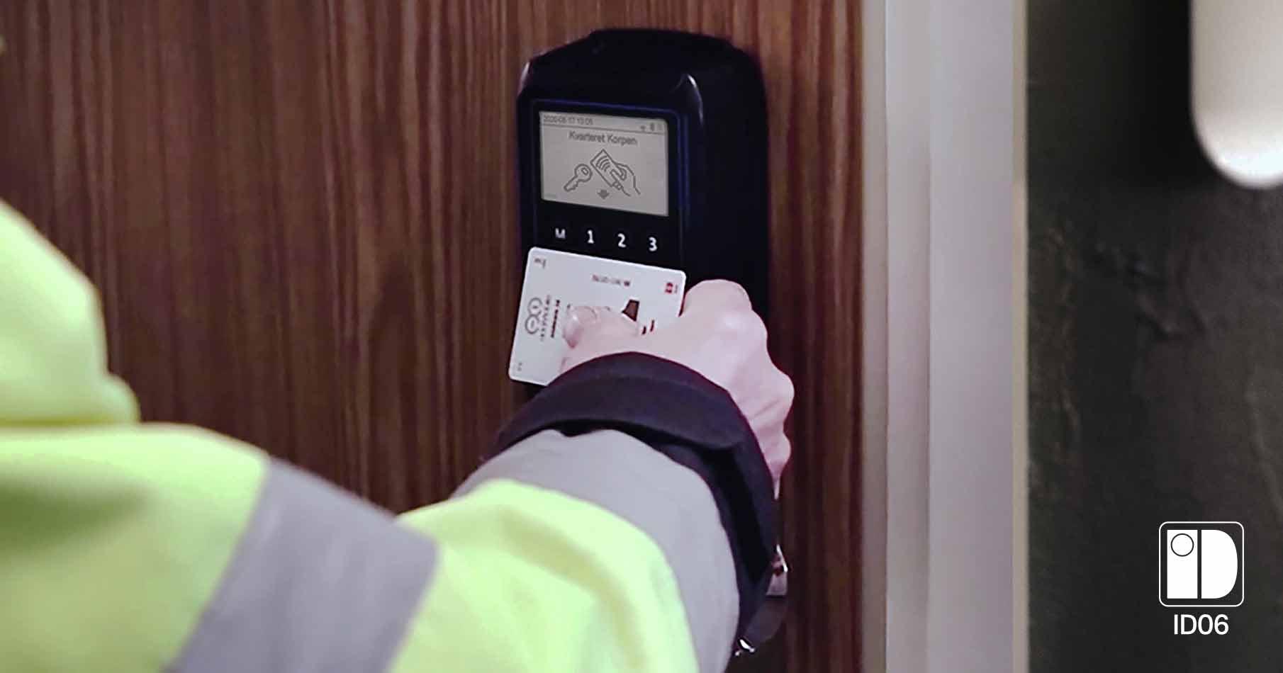 Byggarbetare öppnar en lägenhetsdörr med sitt ID06-kort på en svart kortläsare