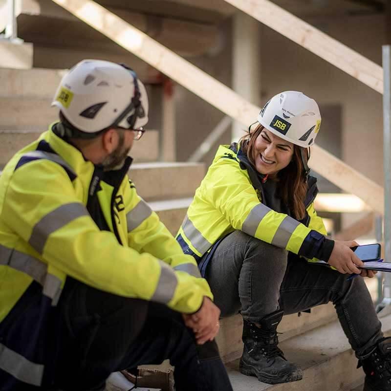 En manlig och en kvinnlig byggarbetare i gula arbetsjackor, vita hjälmar och svarta byxor sitter på en cementtrappa på en byggarbetsplats och samtalar. Kvinnan skrattar.
