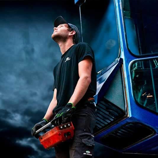 Man i svarta arbetskläder står framför en blå byggkran och fjärrstyr den med en joystick.