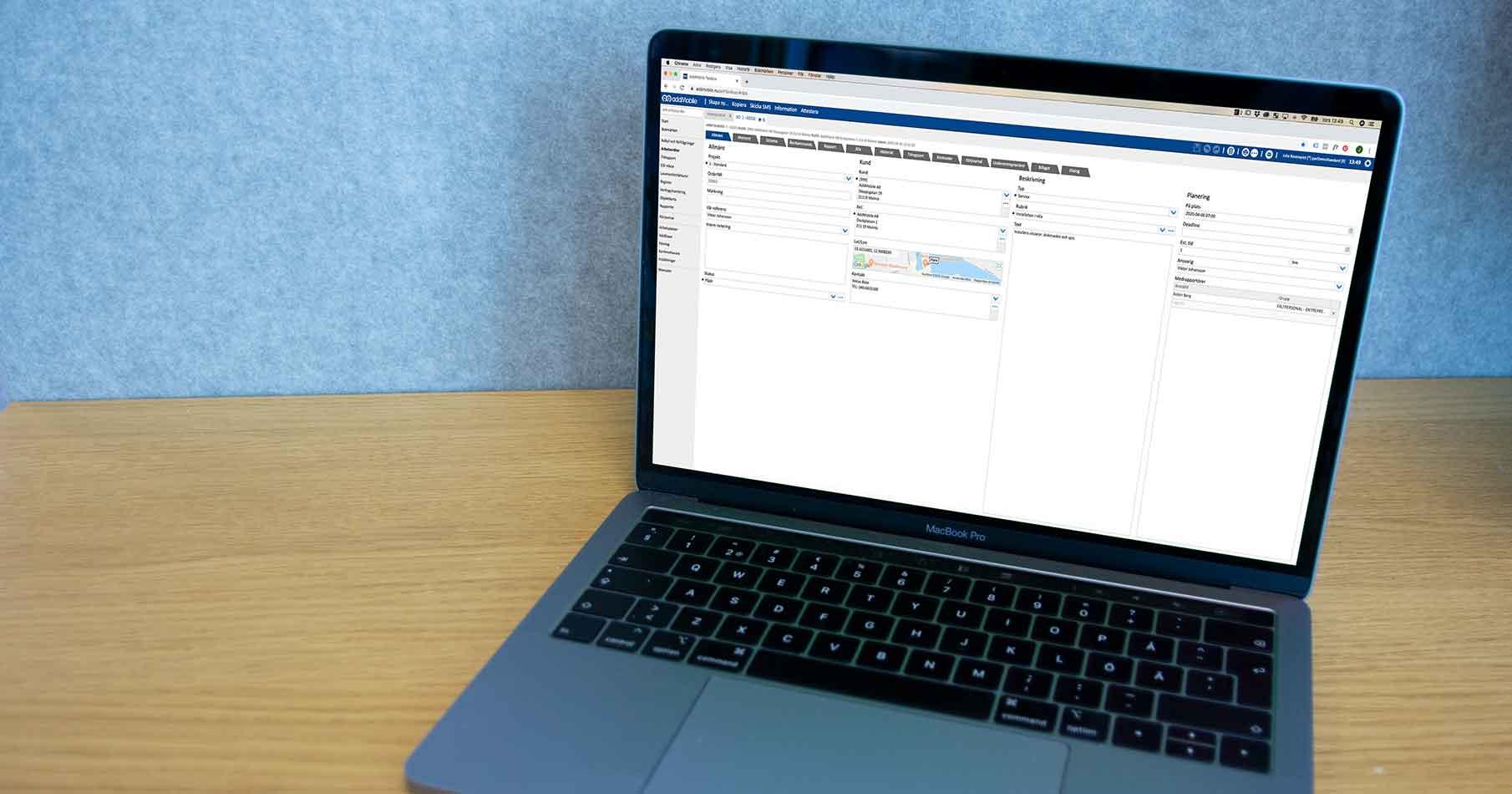 Laptop på skrivbord med AddMobiles projekthanteringssystem på skärmen