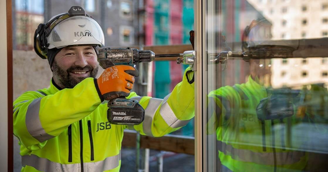 Närbild på en man i vit bygghjälm och gul jacka som skruvar fast ett fönsterhandtag